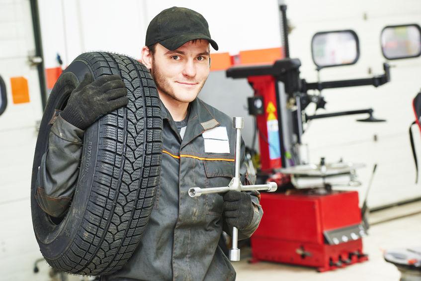 Mechanikerporträt mit Reifen in der Autowerkstatt bei Wartungsarbeiten