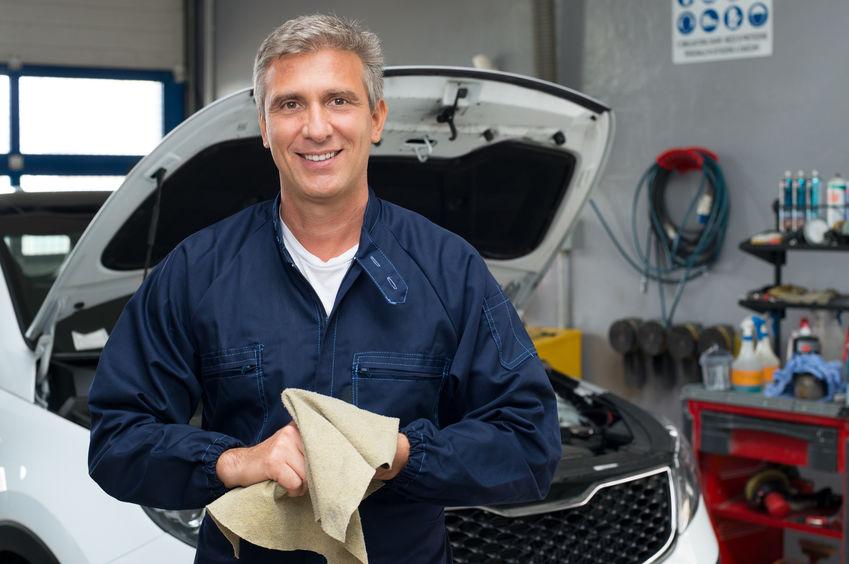Porträt eines Automechanikers, der sich die Hände mit Stoff reinigt
